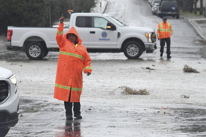 Victorville Public Works staff redirect traffic on Pebble Beach Drive as they closed the roadway due to flooding, Thursday, Dec. (James Quigg/The Daily Press via AP)