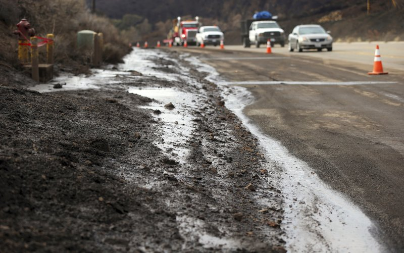 Mud and debris that flowed onto Pacific Cost Highway has closed the right lane in an area burned by the Woolsey Fire in Malibu, Calif. (AP Photo/Reed Saxon)