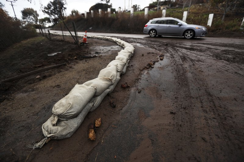 Sandbags help to control mud and debris flow in an area burned by the Woolsey Fire in Malibu, Calif. Thursday, Dec. (AP Photo/Reed Saxon)