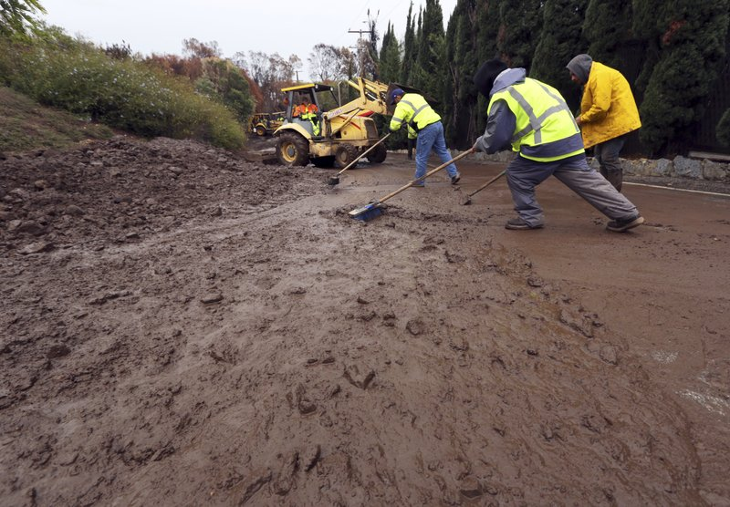 A Malibu Public Works crew clears a culvert on that overflowed with mud and debris on Cuthbert Road in an area burned by the Woolsey fire in Malibu, Calif. (AP Photo/Reed Saxon)