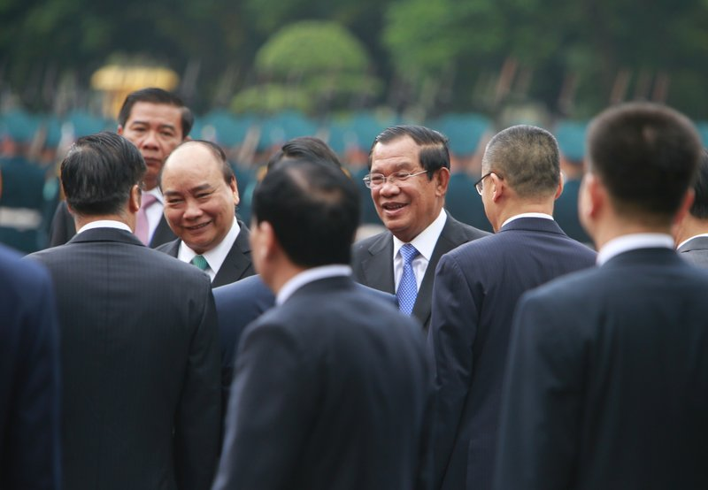 Vietnamese Prime Minister Nguyen Xuan Phuc, center left, introduces Vietnamese officials to Cambodian Prime Minister Hun Sen, center right, in Hanoi, Vietnam Friday, Dec. 7, 2018. Hun Sen is on a three-day visit to boost ties between the two neighboring countries. (AP Photo/Tran Van Minh)