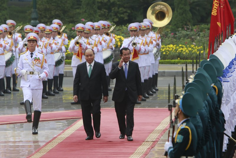 Cambodian Prime Minister Hun Sen, center right, and his Vietnamese counterpart Nguyen Xuan Phuc, center left, review an honor guard in Hanoi, Vietnam Friday Dec. 7, 2018. Hun Sen is on a three-day visit to Vietnam to boost ties between the two neighboring countries. (AP Photo/Tran Van Minh)