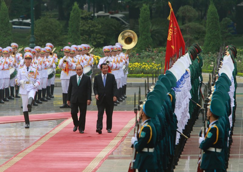 Cambodian Prime Minister Hun Sen, center right, and his Vietnamese counterpart Nguyen Xuan Phuc, center left, review an honor guard in Hanoi, Vietnam Friday, Dec. 7, 2018. Hun Sen is on a three-day visit to boost ties between the two neighboring countries. (AP Photo/Tran Van Minh)