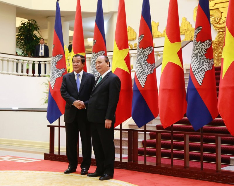 Cambodian Prime Minister Hun Sen, left, shakes hands with his Vietnamese counterpart Nguyen Xuan Phuc before heading for talks behind closed doors in Hanoi, Vietnam Friday, Dec. 7, 2018. Hun Sen is on a three-day visit to boost ties between the two neighboring countries. (AP Photo/Tran Van Minh)