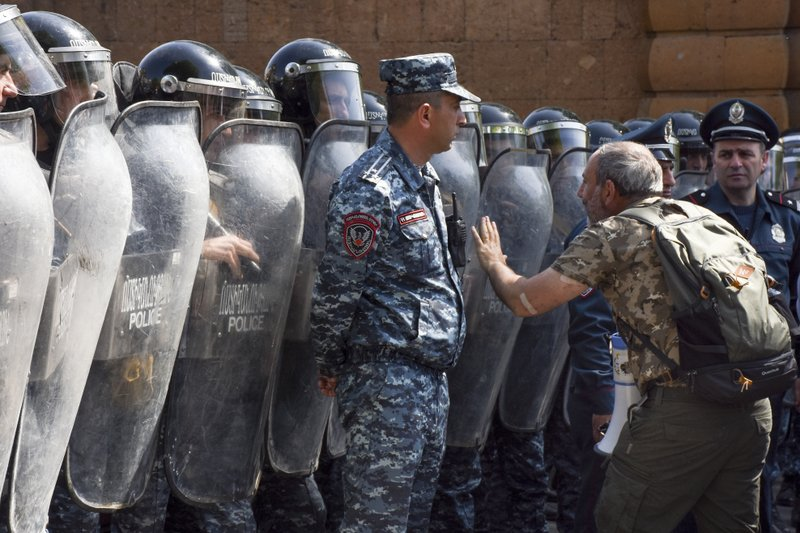 FILE- In this file photo taken on Wednesday, April 18, 2018, Opposition leader Nikol Pashinian, right, speaks to a police officer in front of a police line blocking the way to demonstrators protesting the former president's shift into the prime minister's seat in Yerevan, Armenia. (Narek Aleksanyan, PAN Photo via AP, File)