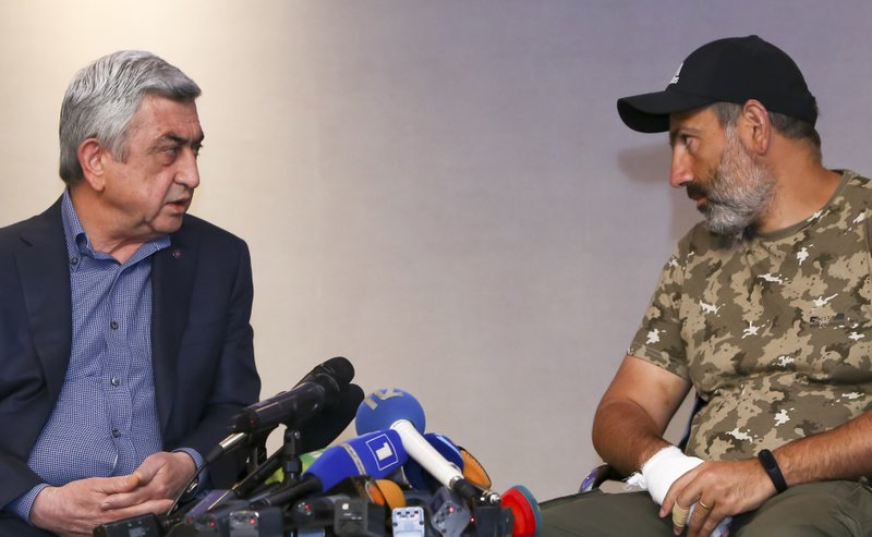 FILE - In this file photo taken on Sunday, April 22, 2018, Former Armenian President Serzh Sargsyan, left, speaks with protest leader Nikol Pashinian during their meeting in Yerevan, Armenia. (Hrant Khachatryan/PAN Photo via AP, File)