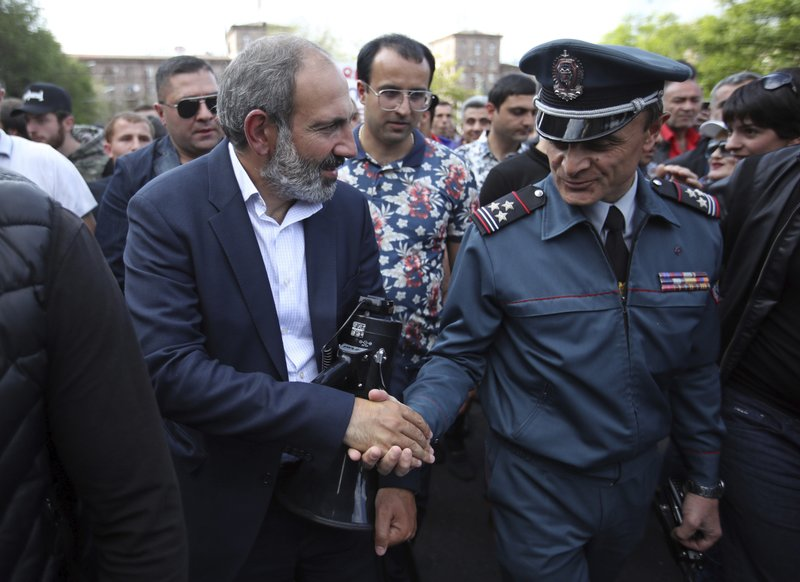 FILE - In this file photo taken on Monday, April 30, 2018, Armenian protest leader Nikol Pashinian, left, shakes hands with a police officer during a rally in Yerevan, Armenia. (AP Photo/Thanassis Stavrakis, File)