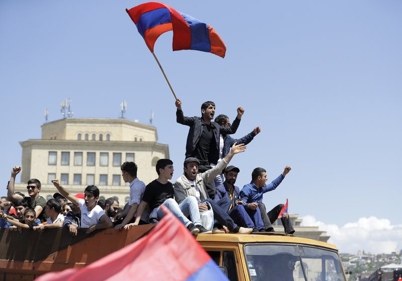 FILE - In this file photo taken on Wednesday, May 2, 2018, Supporters of opposition lawmaker Nikol Pashinian stand atop of a vehicle as they protest in Republic Square in Yerevan, Armenia. (AP Photo/Sergei Grits, File)