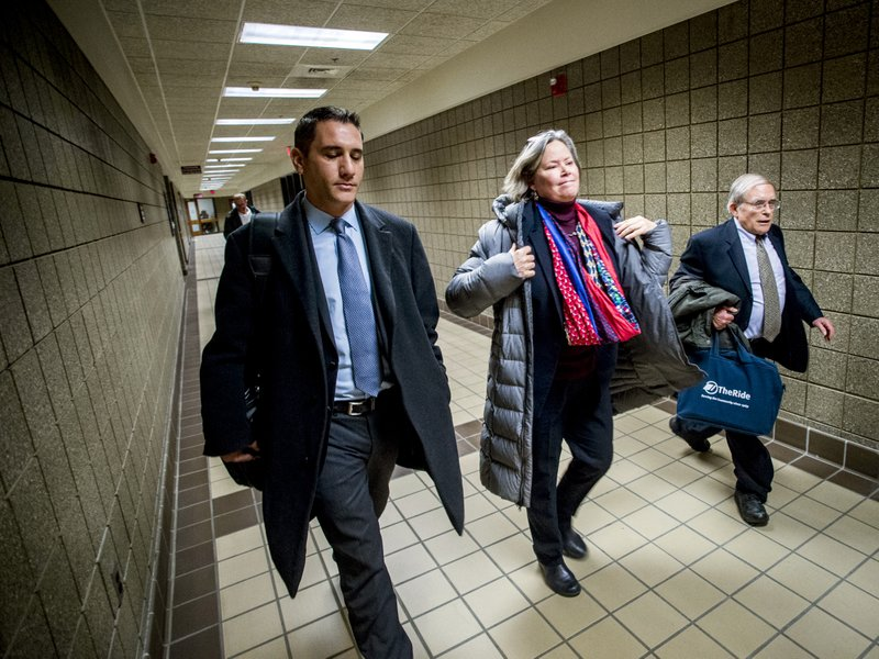 Dr. Eden Wells, center, puts her jacket on as she leaves the court house alongside her defense attorneys Steve Tramontin, left, and Jerold Lax after a hearing Friday, Dec. (Jake May/The Flint Journal via AP)
