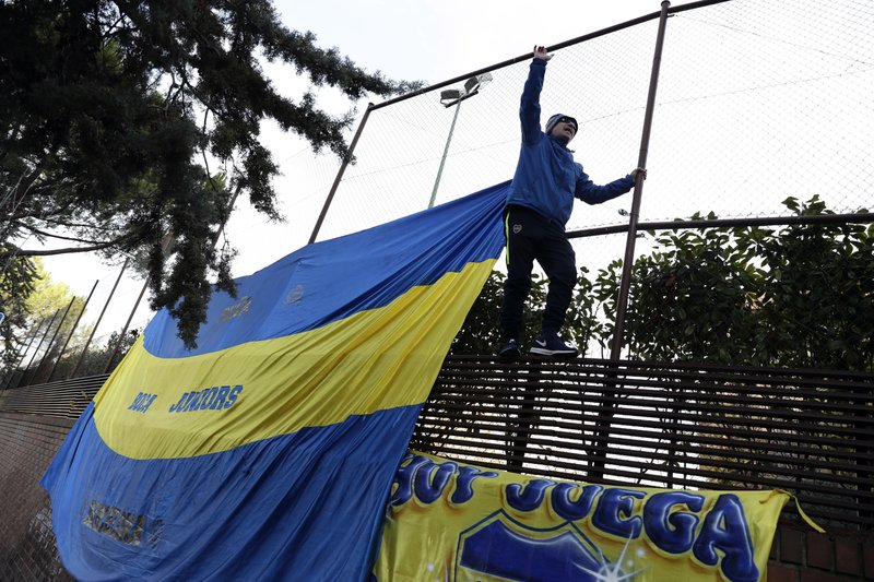 A Boca Juniors supporter climbs on a fence during a gathering of fans outside the team hotel in Madrid Saturday, Dec. (AP Photo/Manu Fernandez)