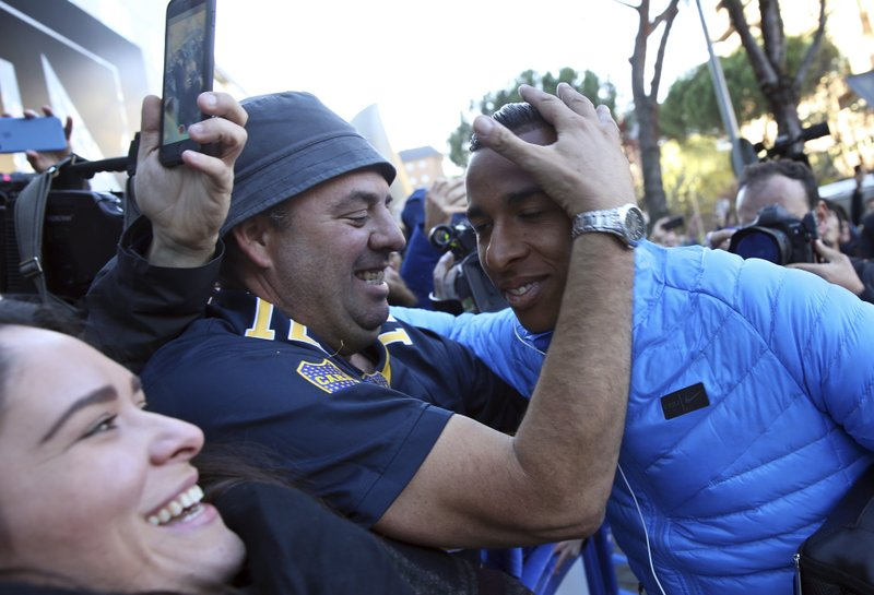 Boca Juniors' Sebastian Villa, right, is hugged by a supporter as the team arrives at their hotel in Madrid Saturday, Dec. (AP Photo/Andrea Comas)