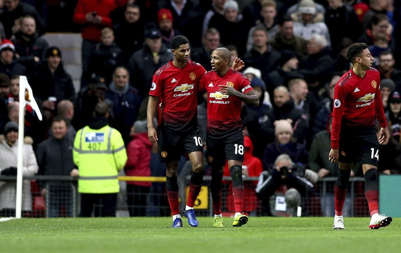 Manchester United's Ashley Young, center right, celebrates scoring his side's first goal of the game with teammate Marcus Rashford during their English Premier League soccer match against Fulham at Old Trafford, Manchester, England, Saturday, Dec. (Barrington Coombs/PA via AP)