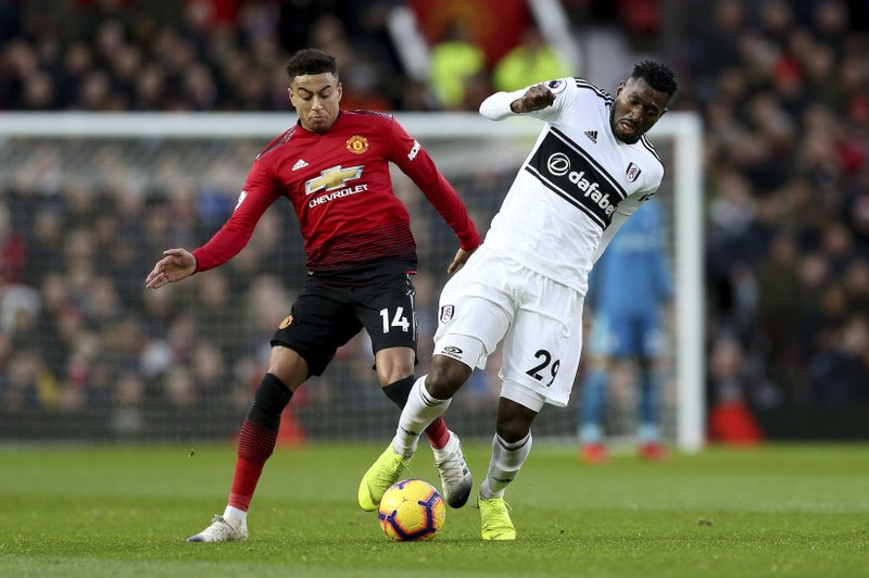 Manchester United's Jesse Lingard, left, and Fulham's Andre-Frank Zambo Anguissa in action during their English Premier League soccer match at Old Trafford, Manchester, England, Saturday, Dec. (Barrington Coombs/PA via AP)