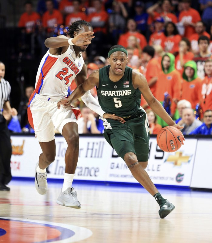 Michigan State guard Cassius Winston (5) dribbles up court past Florida guard Deaundrae Ballard (24) during the first half of an NCAA college basketball game Saturday, Dec. (AP Photo/Matt Stamey)