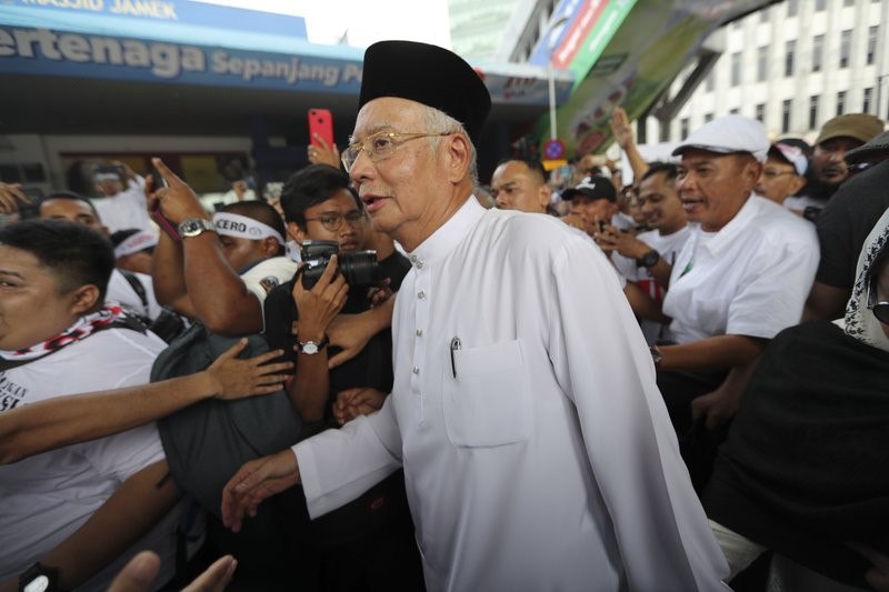 Former Prime Minister Najib Razak arrives for a rally to celebrate the government's move to withdraw plans to ratify a U. (AP Photo/Vincent Thian)