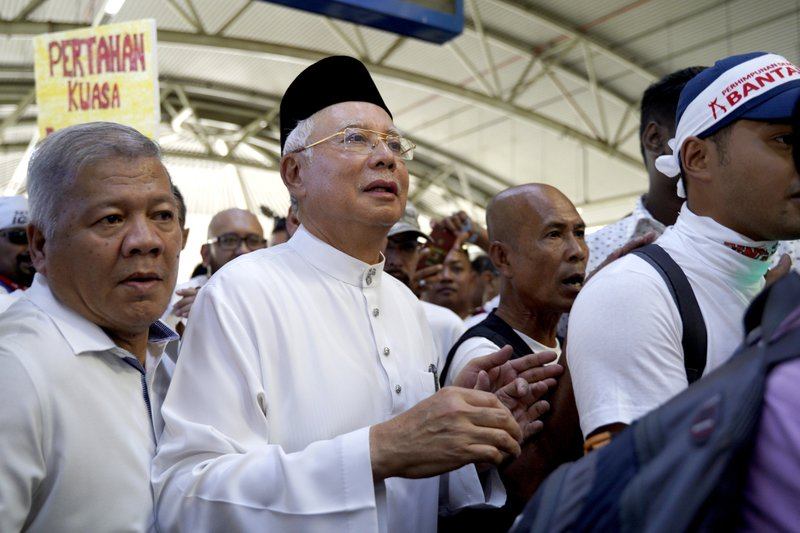 Former Malaysia Prime Minister Najib Razak departs with protesters to attend a rally to celebrate the government's move to withdraw plans to ratify a U. (AP Photo/Yam G-Jun)