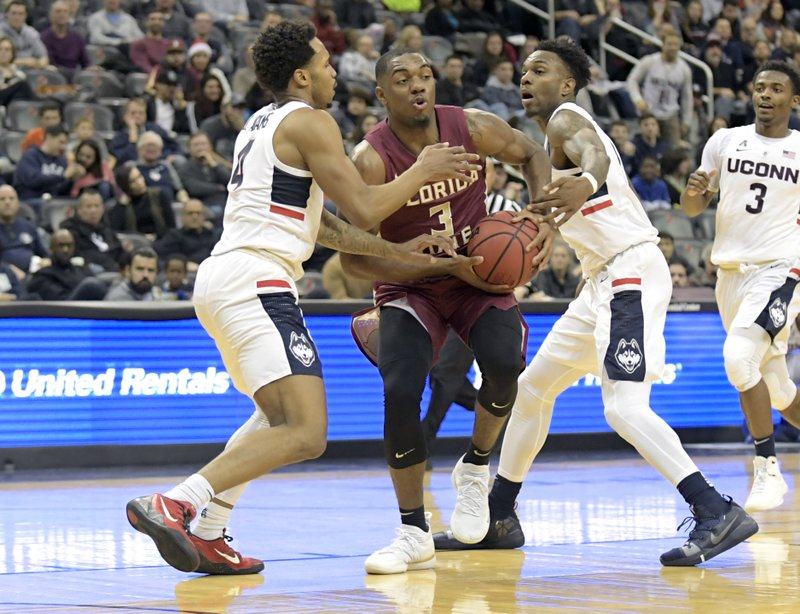 Florida State guard Trent Forrest (3) attempts to split the defense of Connecticut guards Jalen Adams, left, and Tarin Smith, right, during the first half of an NCAA college basketball game in the Never Forget Tribute Classic Saturday, Dec. (AP Photo/Bill Kostroun)
