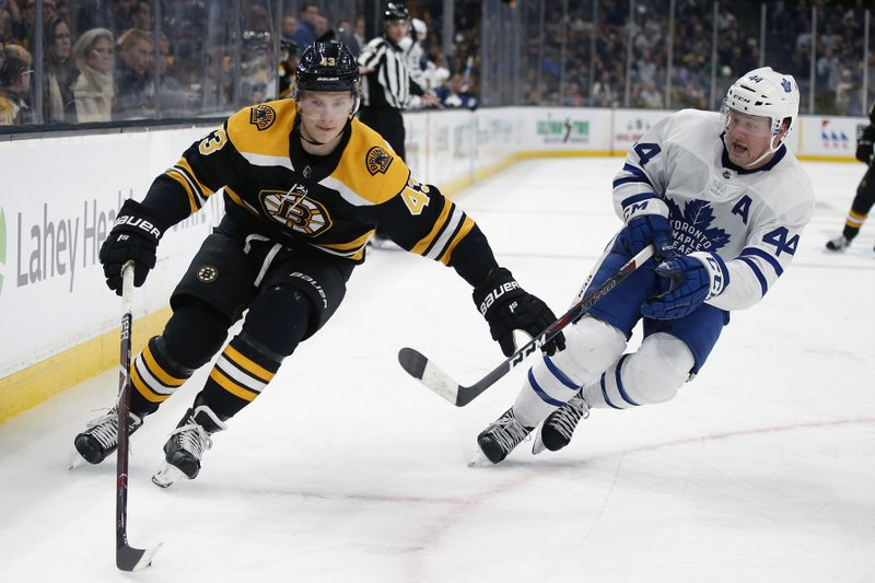 Toronto Maple Leafs' Morgan Rielly (44) defends against Boston Bruins' Danton Heinen (43) during the second period of an NHL hockey game in Boston, Saturday, Dec. (AP Photo/Michael Dwyer)