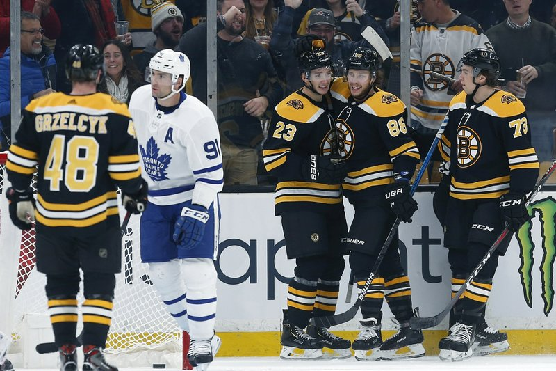 Boston Bruins' Jakob Forsbacka Karlsson (23) celebrates his goal with teammates David Pastrnak (88) and Charlie McAvoy (73) as Toronto Maple Leafs' John Tavares (91) skates away during the first period of an NHL hockey game in Boston, Saturday, Dec. (AP Photo/Michael Dwyer)