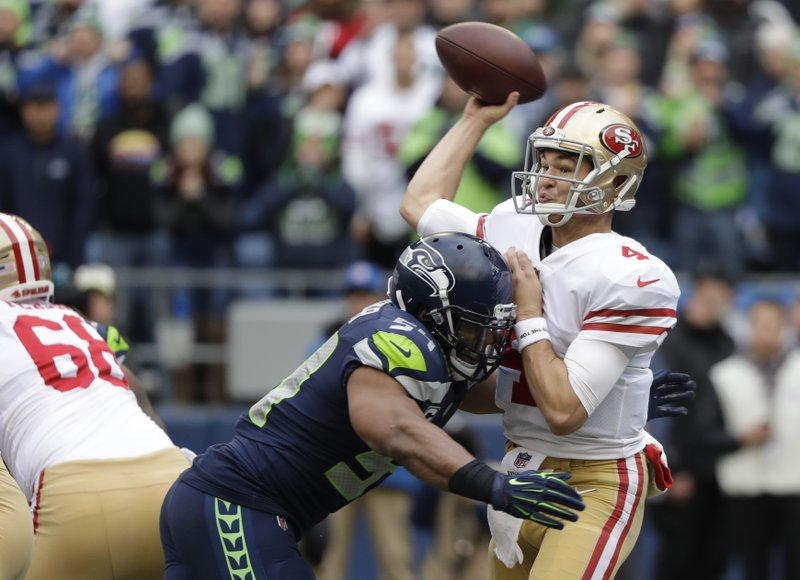 San Francisco 49ers quarterback Nick Mullens passes under pressure from Seattle Seahawks middle linebacker Bobby Wagner during the first half of an NFL football game, Sunday, Dec. (AP Photo/Elaine Thompson)