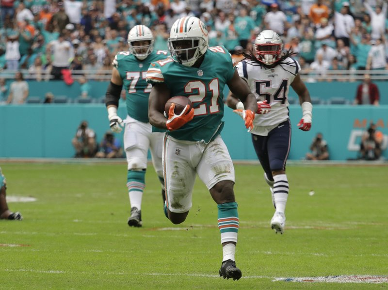 Miami Dolphins running back Frank Gore (21) runs the ball, during the first half of an NFL football game against the New England Patriots, Sunday, Dec. (AP Photo/Lynne Sladky)