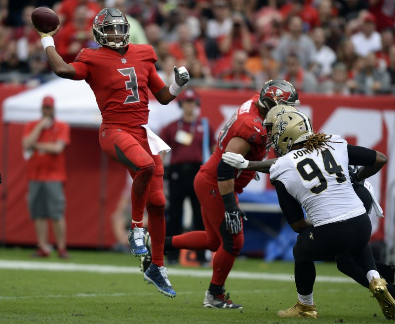 Tampa Bay Buccaneers quarterback Jameis Winston (3) leaps to throw a pass over New Orleans Saints defensive end Cameron Jordan (94) during the first half of an NFL football game Sunday, Dec. (AP Photo/Jason Behnken)