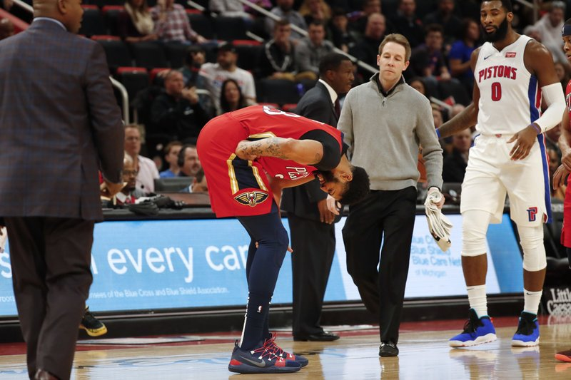 New Orleans Pelicans forward Anthony Davis, center, reacts after being injured in the first half of an NBA basketball game against the Detroit Pistons in Detroit, Sunday, Dec. (AP Photo/Paul Sancya)