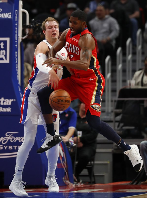 Detroit Pistons guard Luke Kennard, left, knocks the ball from New Orleans Pelicans guard E'Twaun Moore, right, in the first half of an NBA basketball game in Detroit, Sunday, Dec. (AP Photo/Paul Sancya)