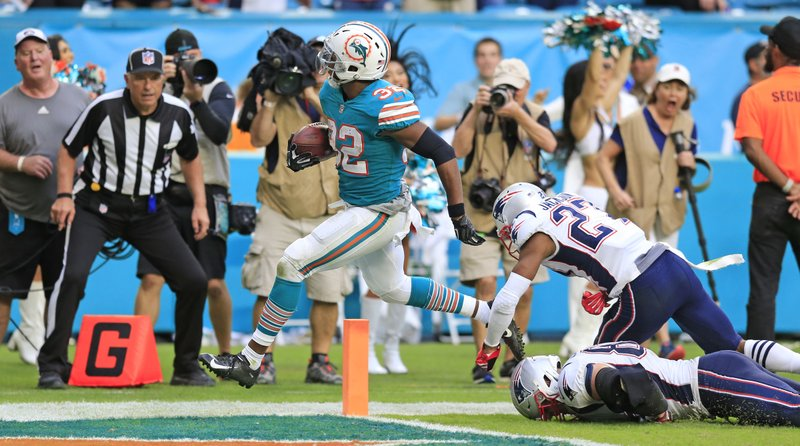 Miami Dolphins running back Kenyan Drake (32) scores to defeat the New England Patriots at Hard Rock Stadium in Miami Gardens on Sunday, Dec. (Al Diaz/Miami Herald via AP)