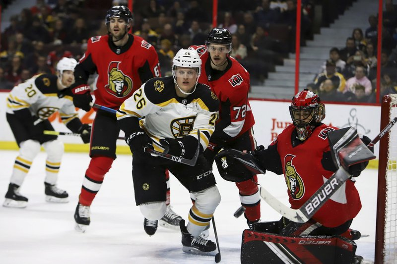 Boston Bruins centre Colby Cave (26) skates towards a puck flying wide of Ottawa Senators goaltender Mike McKenna (33) during first period NHL hockey action in Ottawa on Sunday, Dec. (Fred Chartrand/The Canadian Press via AP)