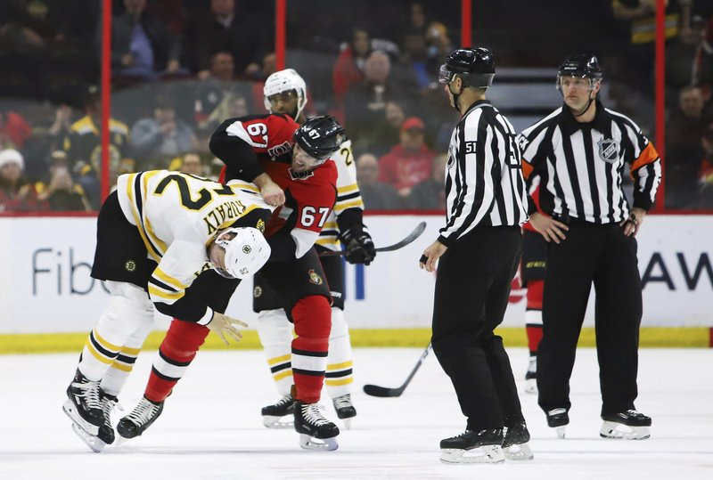 Boston Bruins centre Sean Kuraly (52) gets taken to the ice by Ottawa Senators defenseman Ben Harpur (67)during second period NHL hockey action in Ottawa on Sunday, Dec. (Fred Chartrand/The Canadian Press via AP)