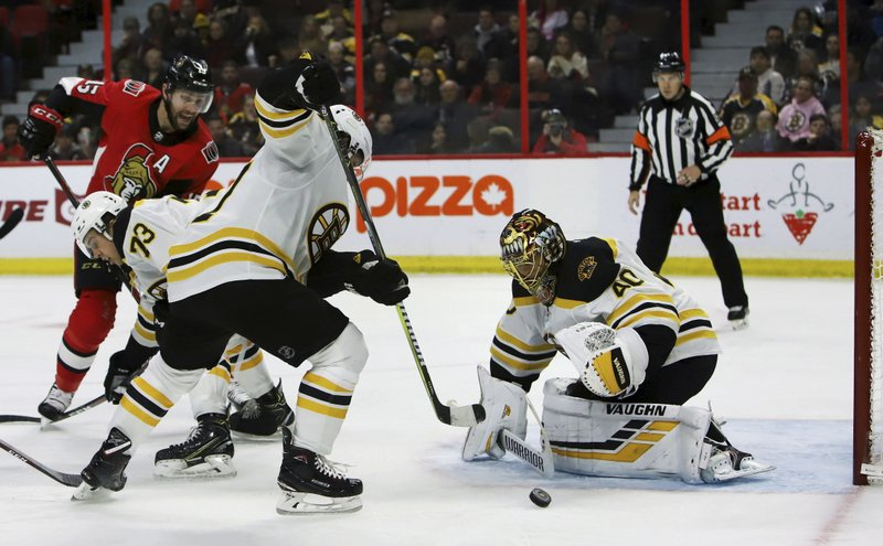 Boston Bruins goaltender Tuukka Rask (40) looks to scoop up a loose puck in front of the net during second period NHL hockey action against the Ottawa Senators, in Ottawa on Sunday, Dec. (Fred Chartrand/The Canadian Press via AP)