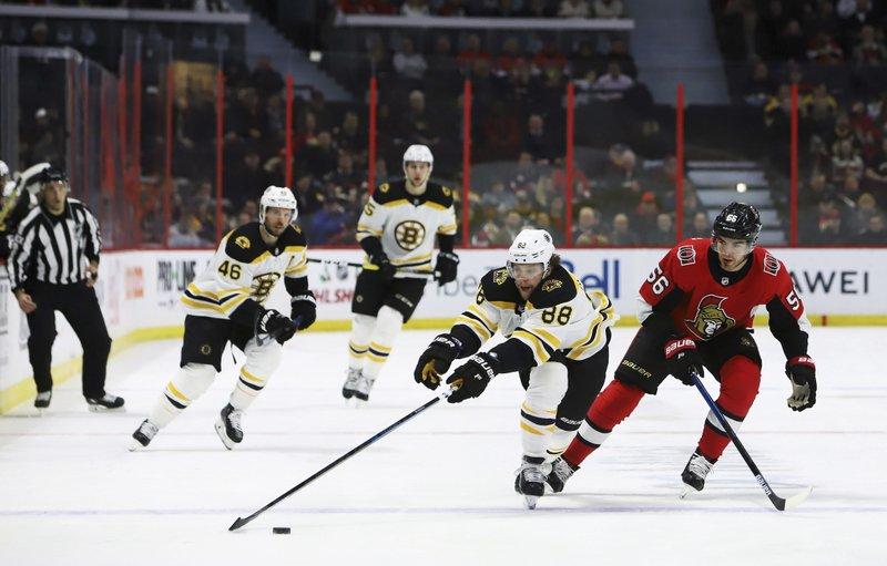 Boston Bruins right wing David Pastrnak (88) reaches far for the puck under pressure from Ottawa Senators left wing Magnus Paajarvi (56) during first-period NHL hockey game action in Ottawa, Ontario, Sunday, Dec. (Fred Chartrand/The Canadian Press via AP)