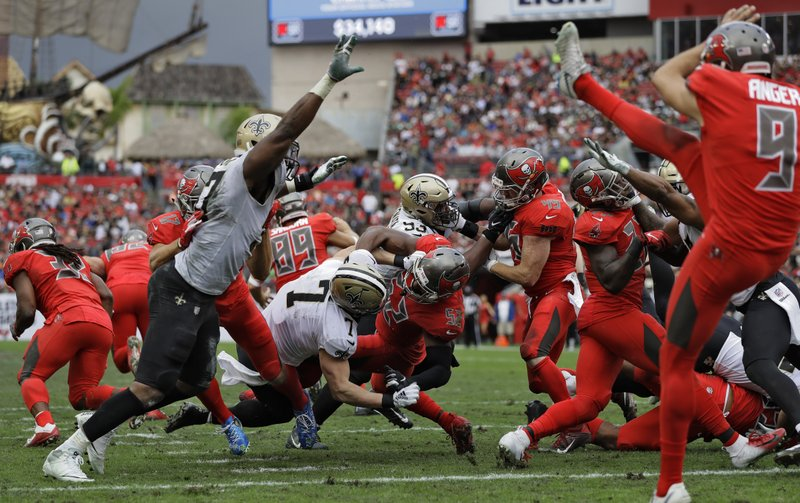 New Orleans Saints Taysom Hill (7) goes down after blocking a punt by Tampa Bay Buccaneers' Bryan Anger during the second half of an NFL football game Sunday, Dec. (AP Photo/Mark LoMoglio)