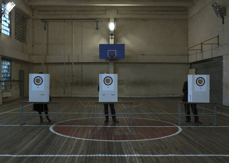 Armenians fill their ballot papers at a polling station during an early parliamentary election in Yerevan, Armenia, Sunday, Dec. (Vahan Stepanyan/PAN Photo via AP)