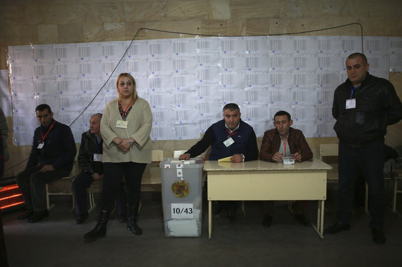 Election officials wait for voters in a polling station during an early parliamentary election in Yerevan, Armenia, Sunday, Dec. (Vahan Stepanyan/PAN Photo via AP)