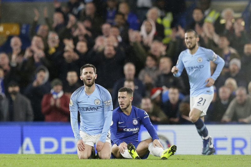 Manchester City's Bernardo Silva, left, gestures after he tackled Chelsea's Eden Hazard, center, during the English Premier League soccer match between Chelsea and Manchester City at Stamford Bridge in London, Saturday Dec. (AP Photo/Tim Ireland)