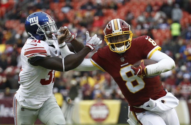 Washington Redskins quarterback Josh Johnson (8) tries to get away from New York Giants defensive back Michael Thomas (31) during the second half of an NFL football game Sunday, Dec. (AP Photo/Patrick Semansky)