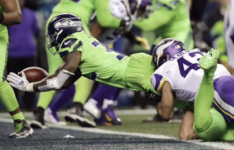 Seattle Seahawks' Chris Carson, left, dives into the end zone for a touchdown against the Minnesota Vikings in the second half of an NFL football game, Monday, Dec. (AP Photo/Ted S. Warren)