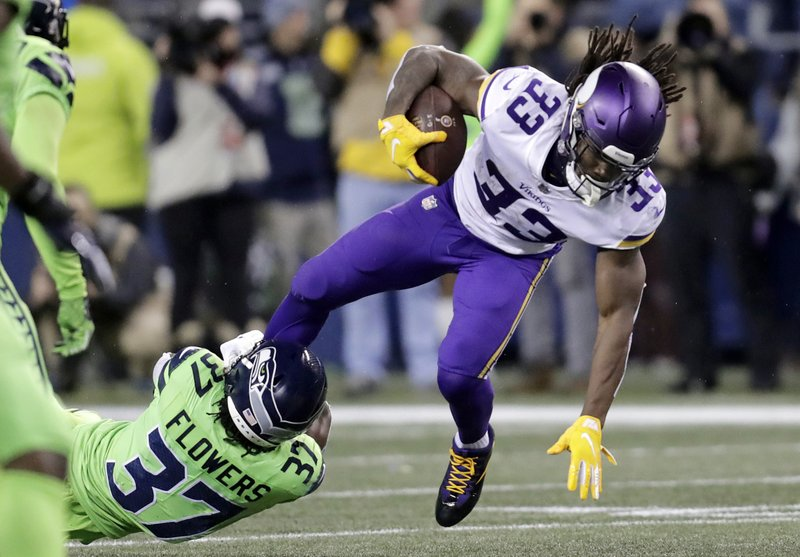Minnesota Vikings' Dalvin Cook runs with the ball as Seattle Seahawks' Tre Flowers tries to bring him down in the first half of an NFL football game, Monday, Dec. (AP Photo/Stephen Brashear)