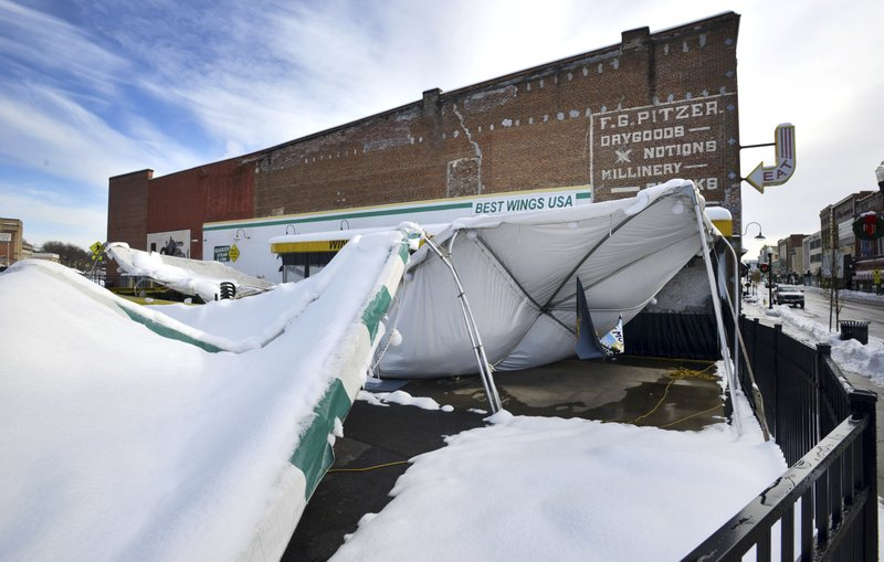 The awning covering the outside seating area at the Quaker Steak and Lube restruarant on State Street in Bristol, Virginia collapsed under the weight of the heavy snowfall. (AP Photo, David Crigger/The Bristol Herald-Courier via AP)