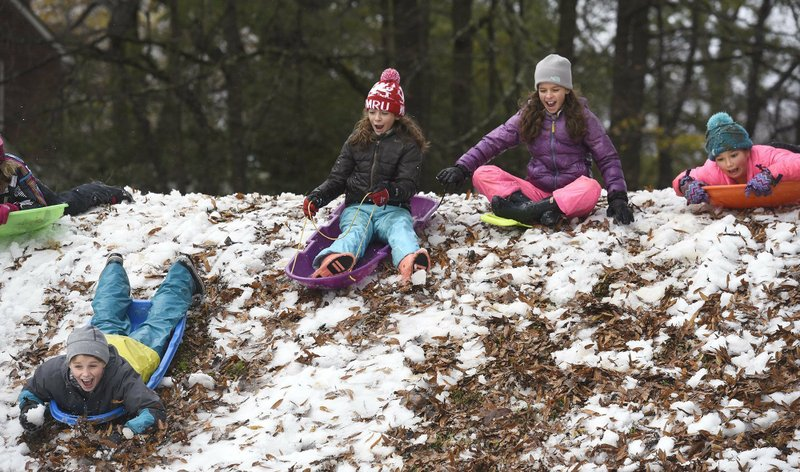 From left; Katie Pilon, 10, twins Cecilia Caldwell and Annie Caldwell, both 10, and Camilla Hart, 10, slide down a Latta Park hill that has seen it's share of sleds in Charlotte, on Monday, Dec. (John D. Simmons/The Charlotte Observer via AP)