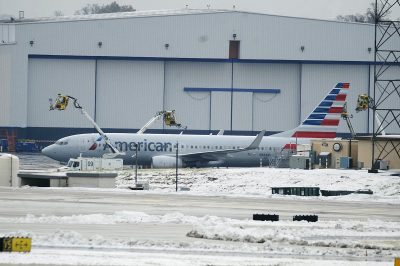 Crews move equipment into position to de-ice airplanes at Charlotte Douglas International Airport despite snowy conditional on Monday, December 10, 2018 in Charlotte, N. (David T. Foster III/The Charlotte Observer via AP)