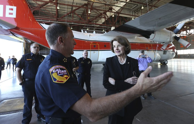 File - In this Nov. 1, 2018, file photo, U. S. Sen. Dianne Feinstein listens as Ken Pimlott, director of the California Department of Forestry and Fire Protection, left, discusses the addition of the C130 air tankers Feinstein succeeded in having transferred from the federal government to the state during a tour in Sacramento, Calif. (AP Photo/Rich Pedroncelli, File)