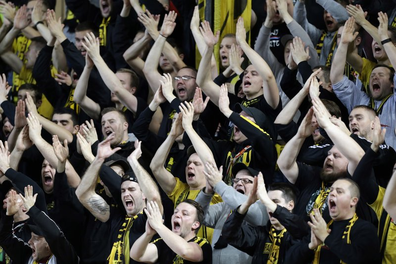 Dortmund's supporters react after Raphael Guerreiro scored his side first goal during the Champions League group A soccer match between AS Monaco and Borussia Dortmund, in Monaco, Tuesday, Dec. (AP Photo/Claude Paris)