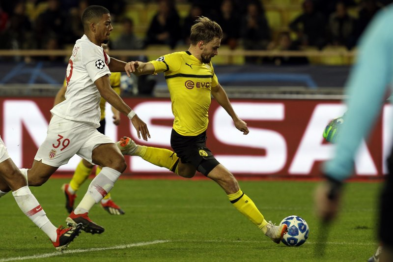 Dortmund's Marcel Schmelzer, right, fights for the ball with Monaco defender Benjamin Henrichs during the Champions League group A soccer match between AS Monaco and Borussia Dortmund, in Monaco, Tuesday, Dec. (AP Photo/Claude Paris)