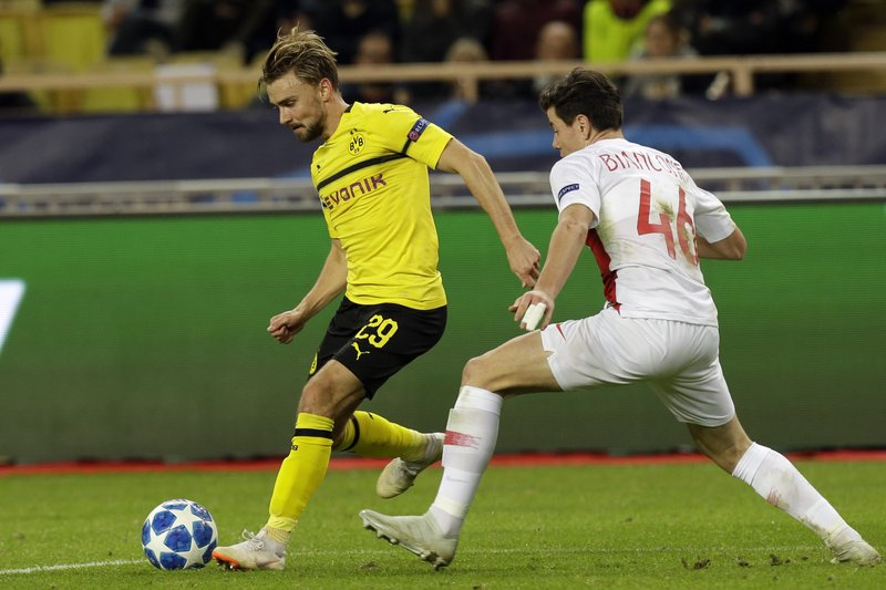 Dortmund's Marcel Schmelzer, left, fights for the ball with Monaco Giulian Biancone during the Champions League group A soccer match between AS Monaco and Borussia Dortmund, in Monaco, Tuesday, Dec. (AP Photo/Claude Paris)