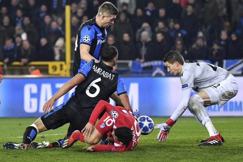Brugge goalkeeper Ethan Horvath, right, defender Luan Peres, rear, midfielder Sofyan Amrabat, center, fights for the ball with Atletico forward Angel Correa during their Champions League group A soccer match between Club Brugge and Atletico Madrid at the Jan Breydel Stadium in Bruges, Belgium, Tuesday, Dec. (AP Photo/Geert Vanden Wijngaert)