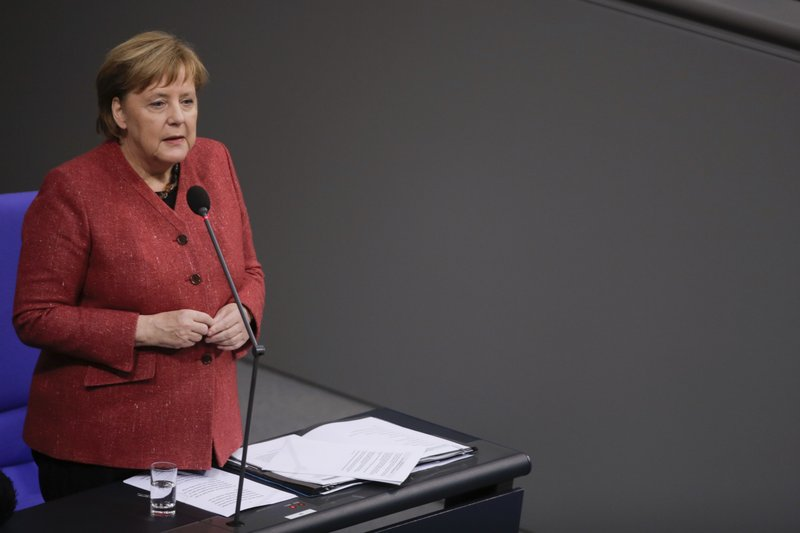 German Chancellor Angela Merkel answers questions of lawmakers during a parliament session of the Bundestag in Berlin, Wednesday, Dec. (AP Photo/Markus Schreiber)