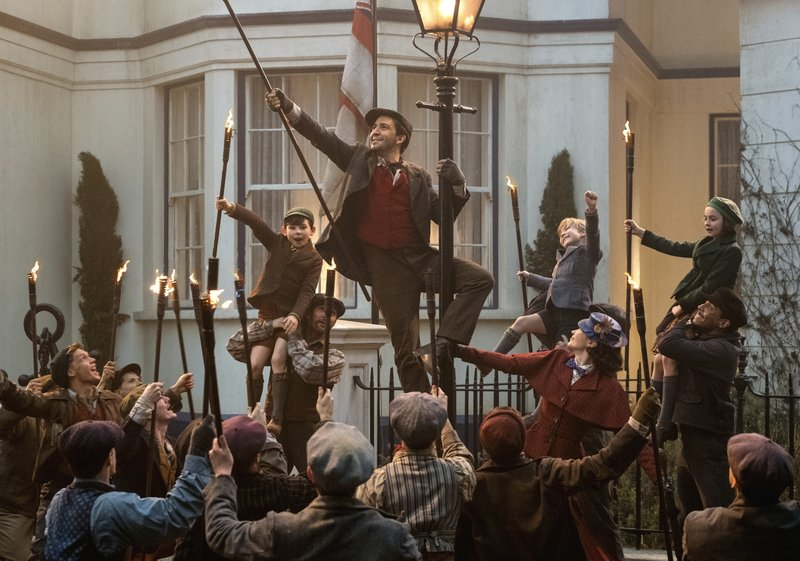 This image released by Disney shows Lin-Manuel Miranda, center, and Emily Blunt as Mary Poppins in